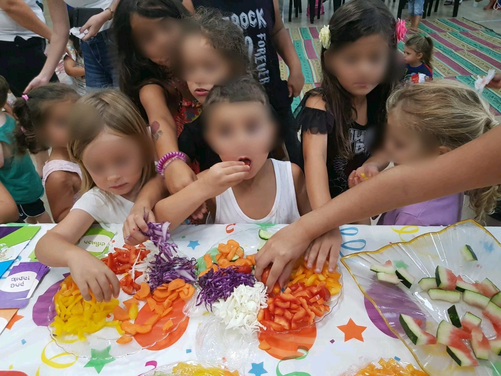 ילדים משחקים ואוכלים ירקות ופירות בהנאה