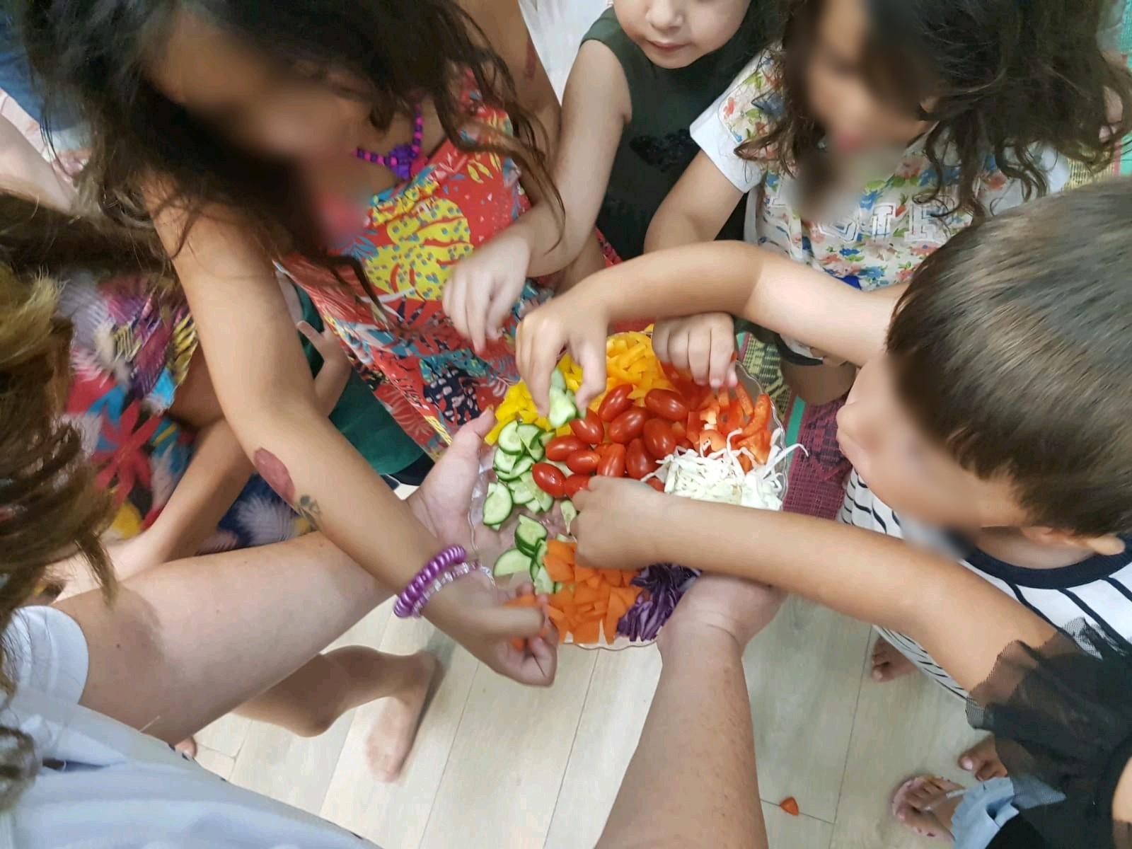 ילדים משחקים ואוכלים בהנאה ירקות ופירות