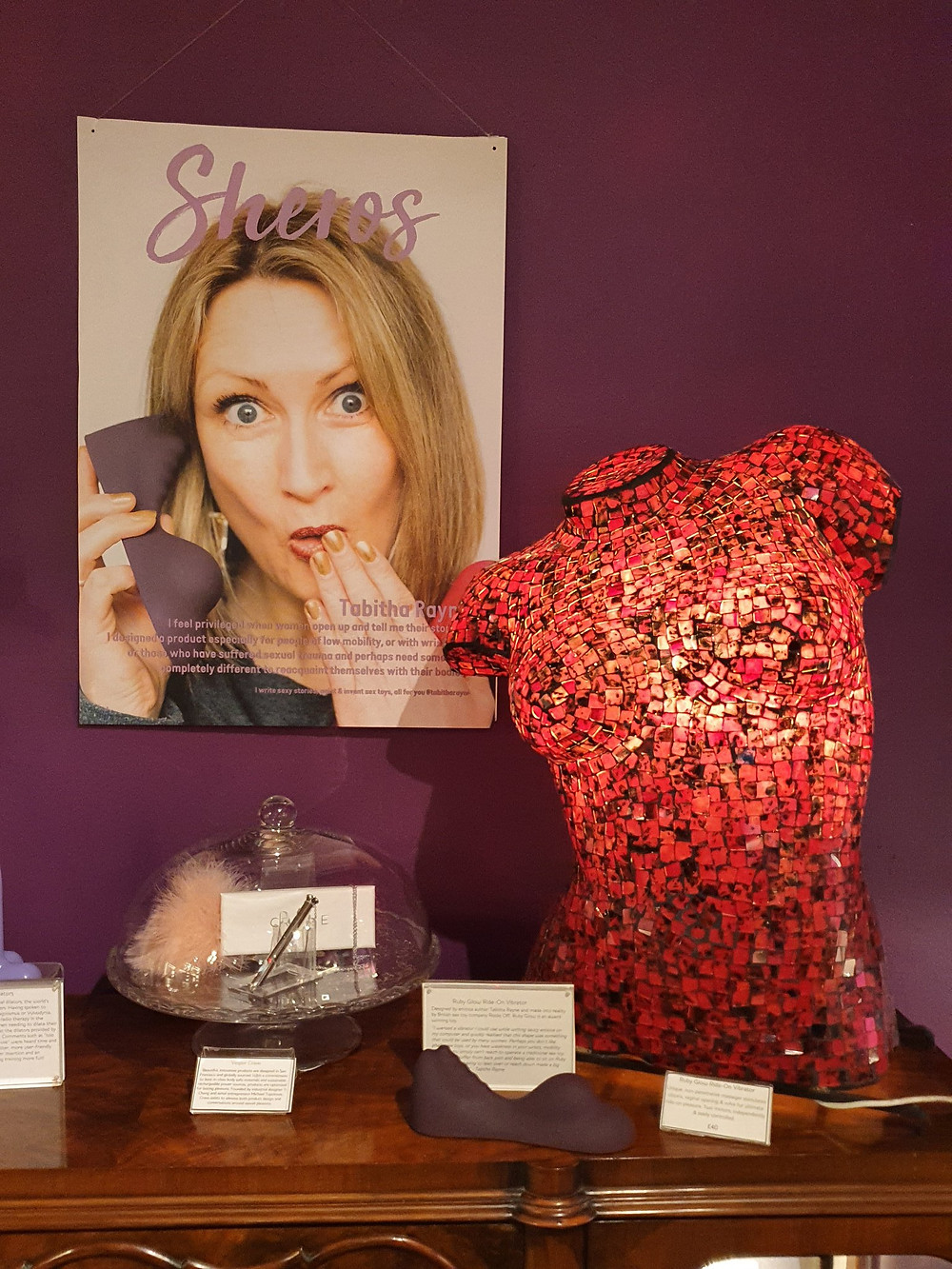 a display with a poster of Tabitha Rayne for the Sh WOmenstore sheros evening - a light up red mosiac torso to the right and a Ruby Glow Dusk middle bottom