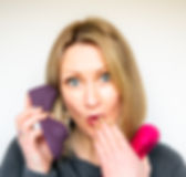 Tabitha Rayne, Ruby Glow inventor making a cheeky exprssin as she holds two RubyGlow sex toys up, one as if it i a phone