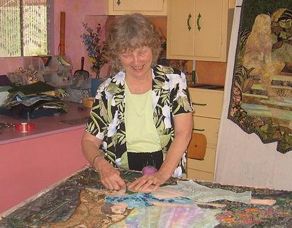woman making art quilt in studio