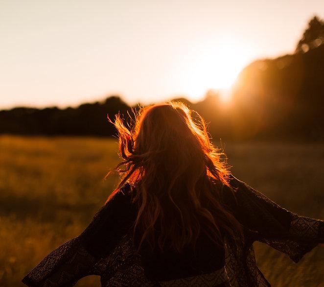 Pige, der løber i felt ved solnedgang