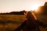 Girl Running in Field at Sunset
