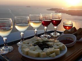 """Санторини имеет уникальные условия для выращивания винограда, который считается экспертами, как самый уникальный винный регион в мире. О Санторини говорят, что здесь вина больше чем воды. Санторини приобрел широкую известность своими винами: сухое белое вино """"Нихтери"""" (из не дозревшего винограда) и """"Винсанто"""" (это красное сладкое вино, которое делается из подсушенного на солнце винограда и обладает очень приятным вкусом). У Вас будет уникальная возможность приобрести сорта вин, которые Вам понравились по цене производителя."""