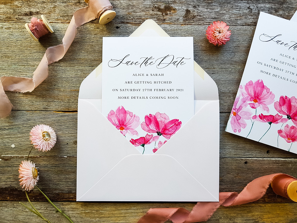 A lovely custom watercolour save the date card featuring watercolour florals in bright pink with a blush envelope