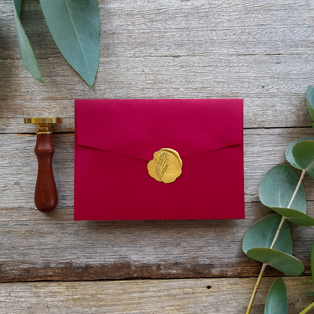 Red envelope with gold wax seal featuring a protea flower