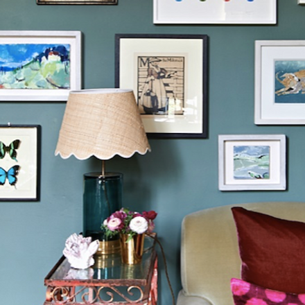 Image of lampshade and base on a side table with lots of pictures on the wall