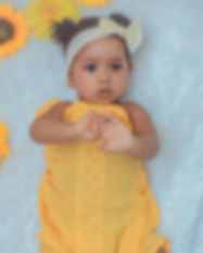 baby in yellow dress lying on white text