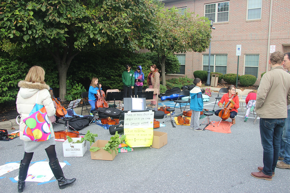 Getting ready.  We used cello cases to hold down our stands.  Did I mention it was windy?!  Vika's dad was kind enough to gather some donations from vendors. A fundraiser by profession, Jack knew that we'd get off to a better start if there were some donations in the boxes.  It encourages people to donate!