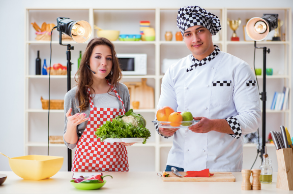 cookery show hosts holding oranges, limes, and cauliflower
