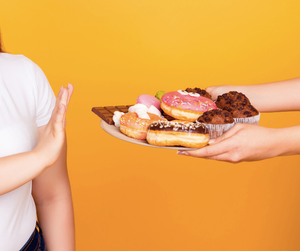 woman turning down snacks, donuts and chocolate