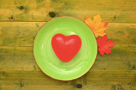heart-shaped food on green plate with green autumn background