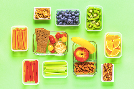 Healthy snack boxes with carrot sticks, nuts, blueberries, kiwis, crackers, hummus and cherry tomatoes and other fruits and vegetables