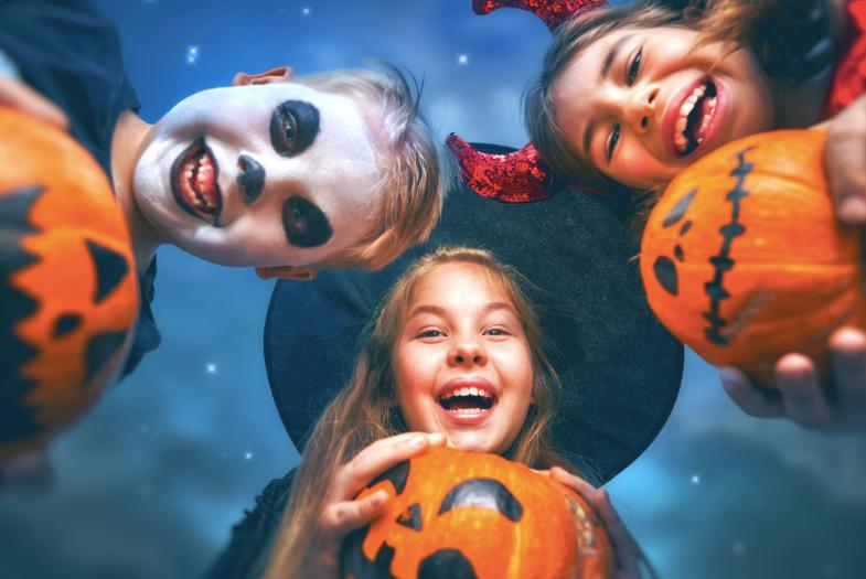 A few children enjoying Halloween holding pumpkin