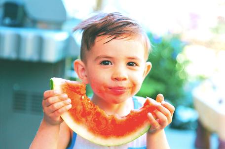 a boy enjoying a watermelon slice