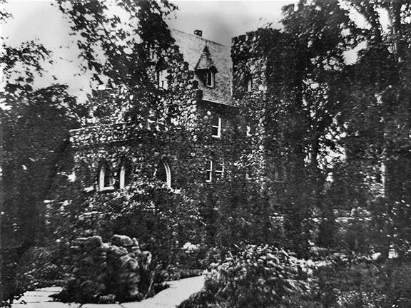 Historic photo of Oeschner's Castle. Photo is fuzzy, but shows the main castle building, a rock sculpture and paths.