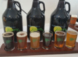 Picture of 3 Summerhill Brewing growlers and a flight of 6 5 ounce beers