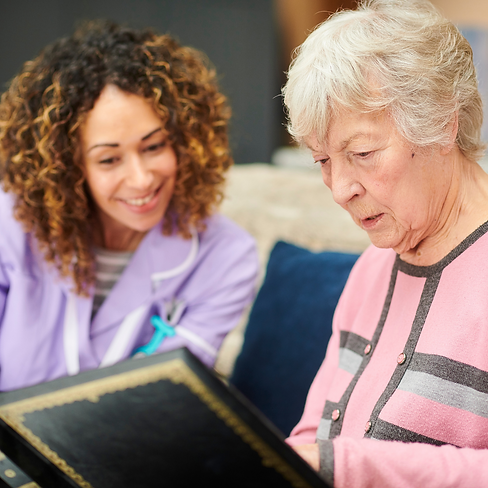Care assistant helping dementia sufferer review memories.