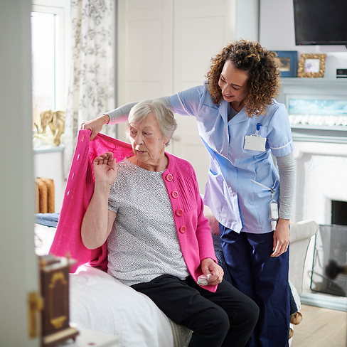 Care assistant helping lady with her cardigan.