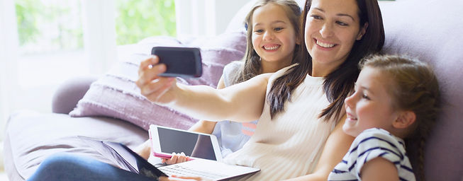 Jeune famille avec tablette et ordinateur portable