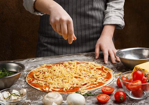preparing-pizza-woman-adding-cheese-to-p
