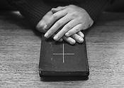 hands-bible-wooden-table.jpg