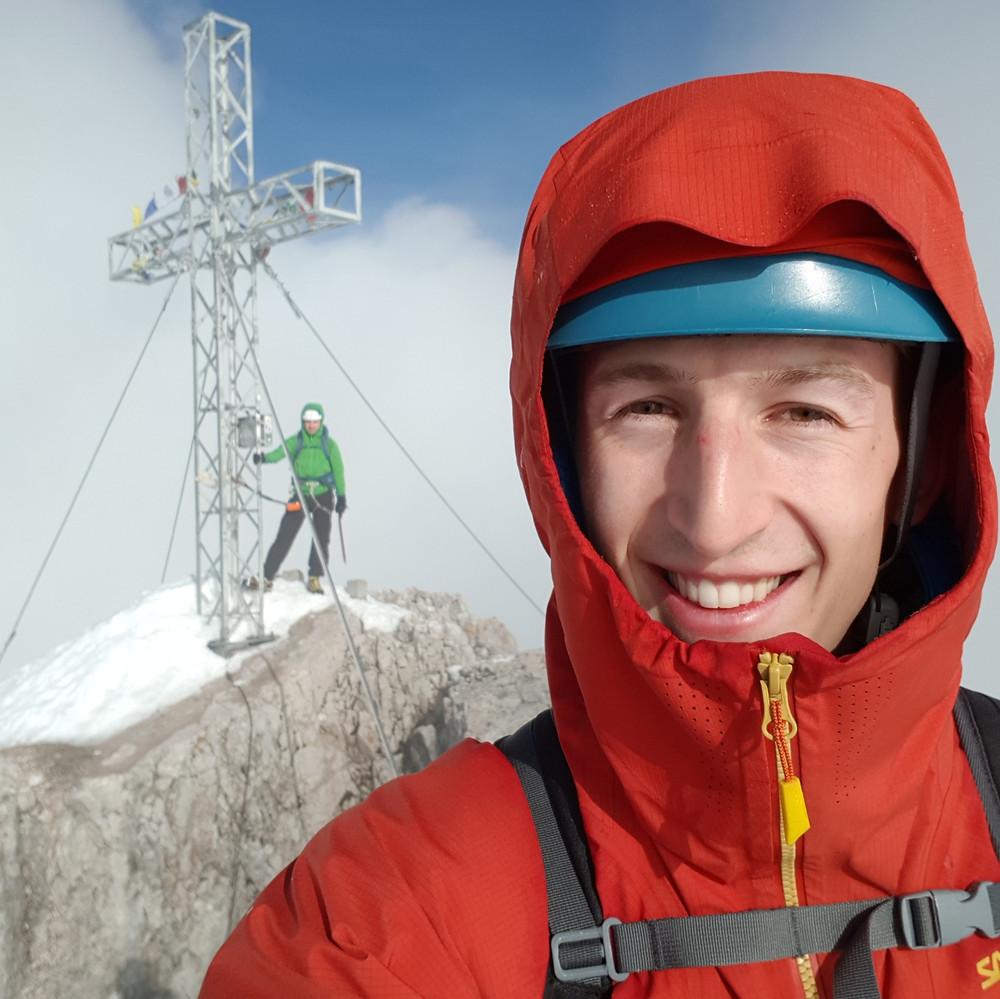 Porträt von Simon Krejci vor einem Gipfelkreuz