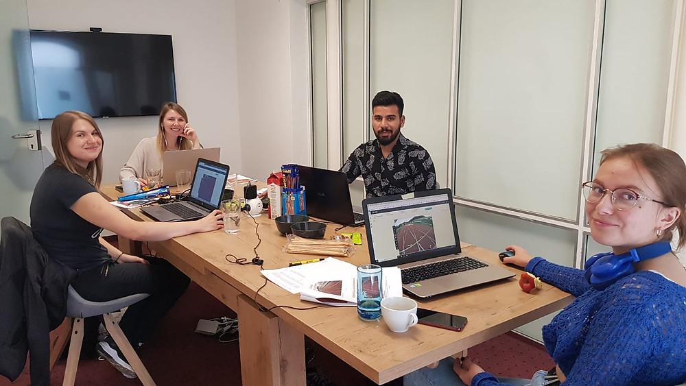 Vier Personen mit Laptops beim Einzeichnen der Linien.