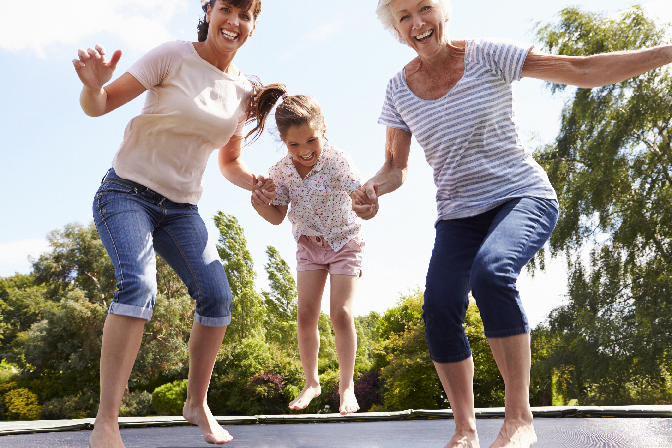 Grandmother, Granddaughter And Mother Bouncing On Trampoline