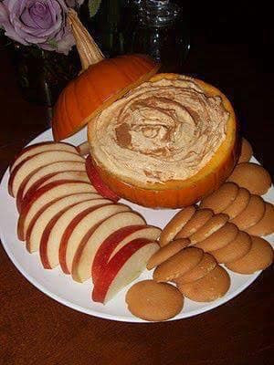 Photograph of a hollowed pumpkin being used as a serving bowl for pumpkin dip.
