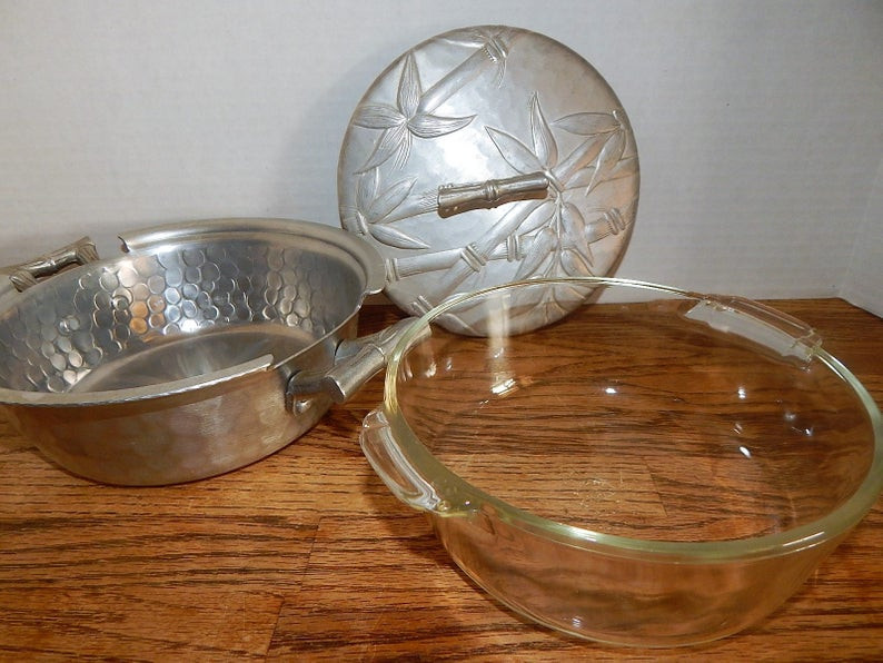 a photo of vintage wrought aluminum tableware, poor mans silver, hammered aluminum mid century dishes, a casserole set by Everlast,