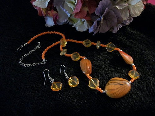 A pretty, shiny amber tiger-striped free form bead is the focal point and centerpiece of this necklace. Orange and silver