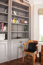 A built-in painted study bookcase and cupboards.
