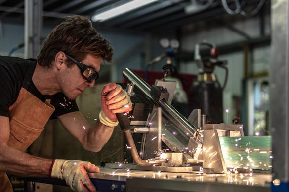 man in bicycle works cutting titanuim tubes