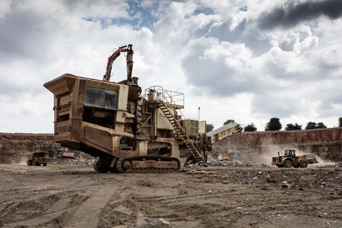 wide shot of quarry with industrial loaders and heavy machinery