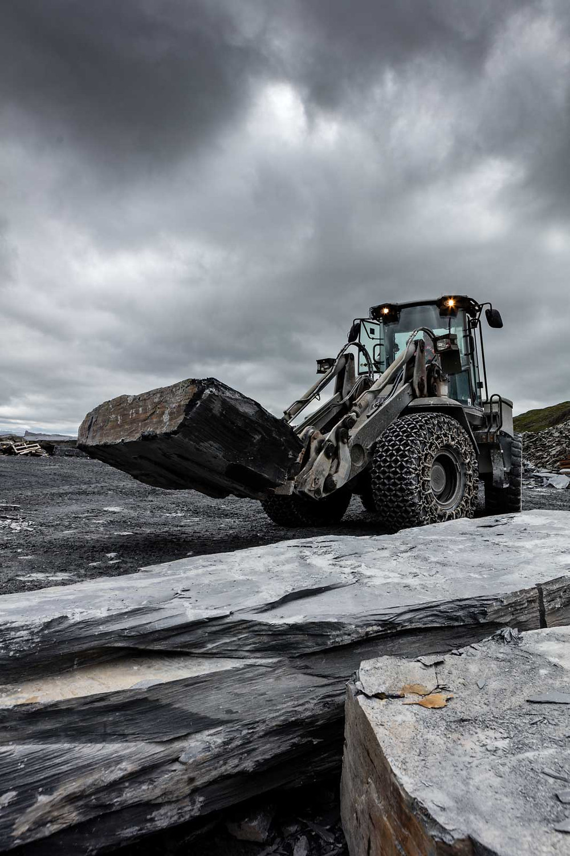 Slate quarry - a loader carries a huge slab of slate.