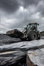 dark moody shot of loader with giant slab of slate
