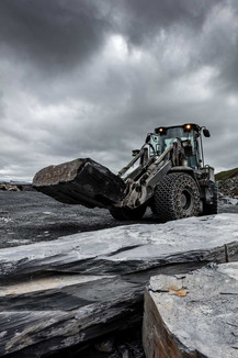dark moody shot of loader with giant slab of slate