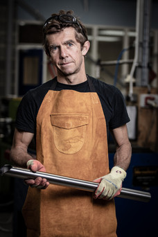 portrait of factory worker with metal tube