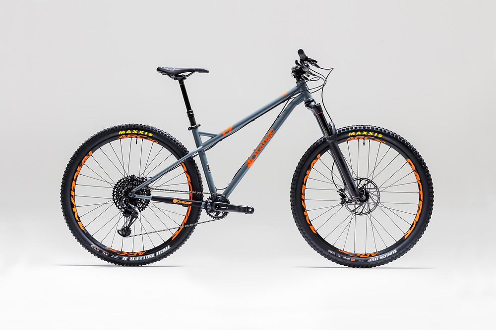 Orange P7 Mountain bike shot in a studio with plain grey background