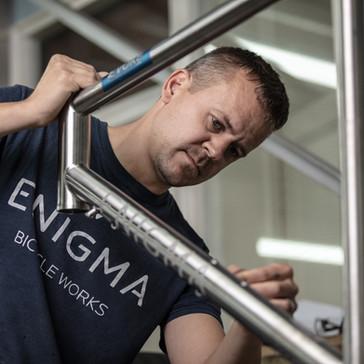 man applying decals on enigma bike frame