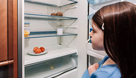Worried girl looking at the almost empty fridge due to a crisis.jpg