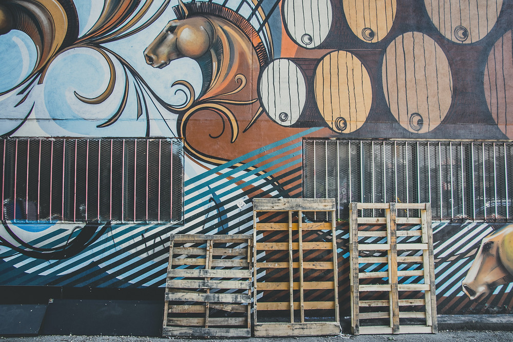 Wooden pallets next to an art wall