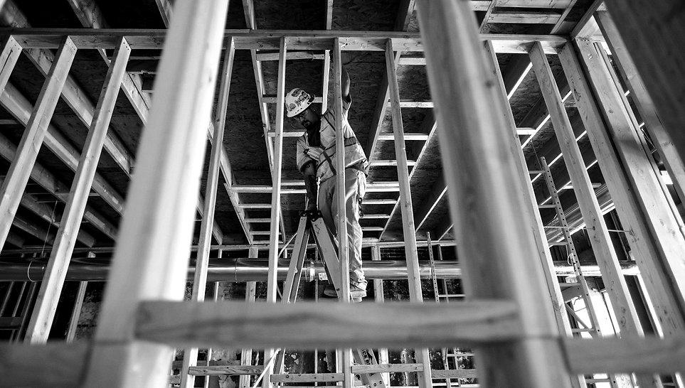 Construction worker on a ladder building framing
