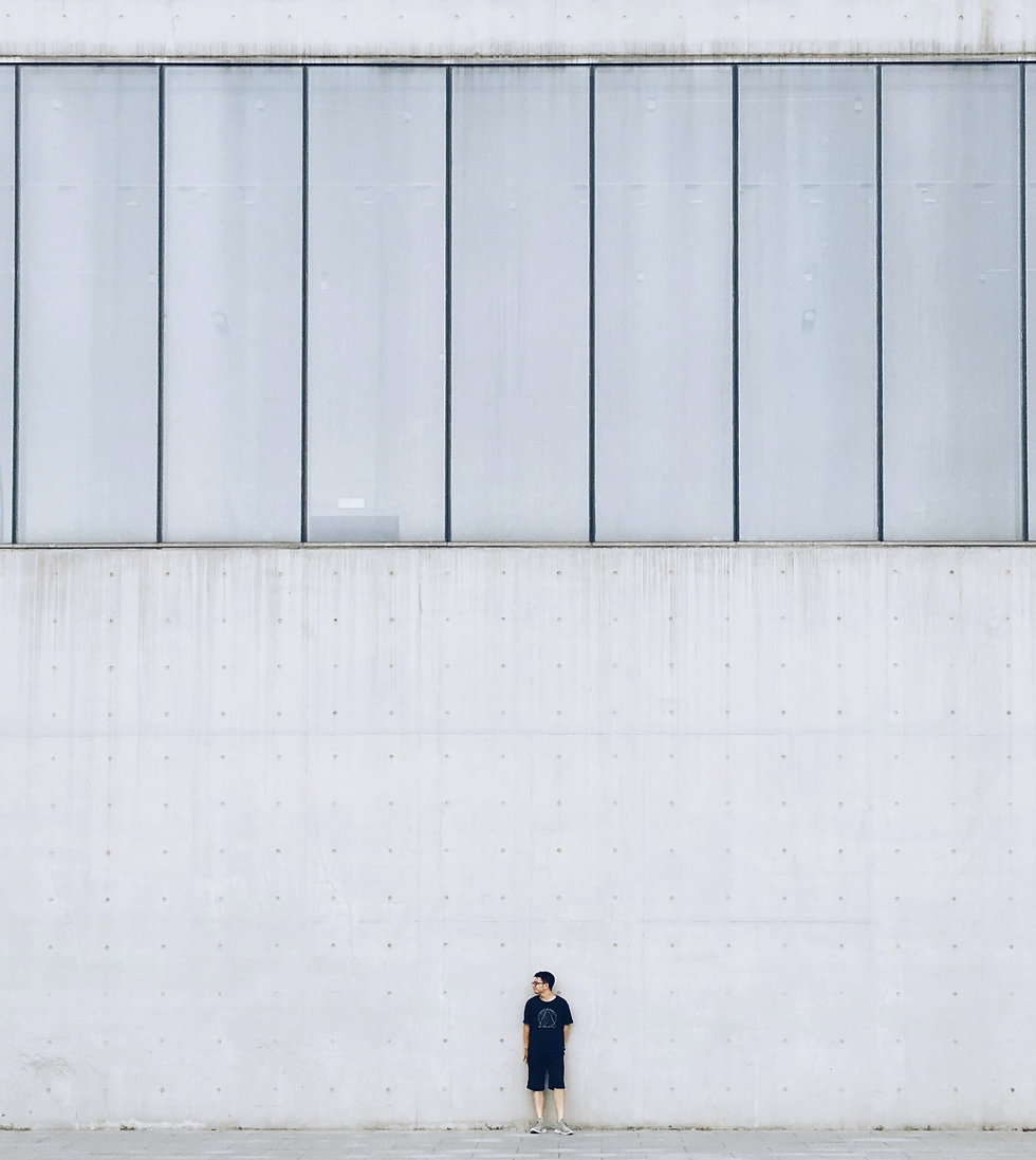 Concrete wall with man standing alone on sidewalk.