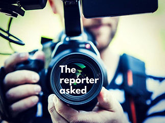 The Reporter Asked by Teresa Compton. Man with camera pointing the camera straight at the viewer.