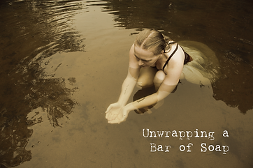"""Unwrapping a Bar of Soap by KKingston. Woman catching water in hands with text, """"Unwrapping a bar of Soap."""""""