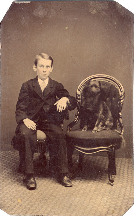 Black and white formal photo of a boy and a dog.