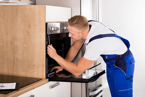 Man fixing oven in blue apron.jpg