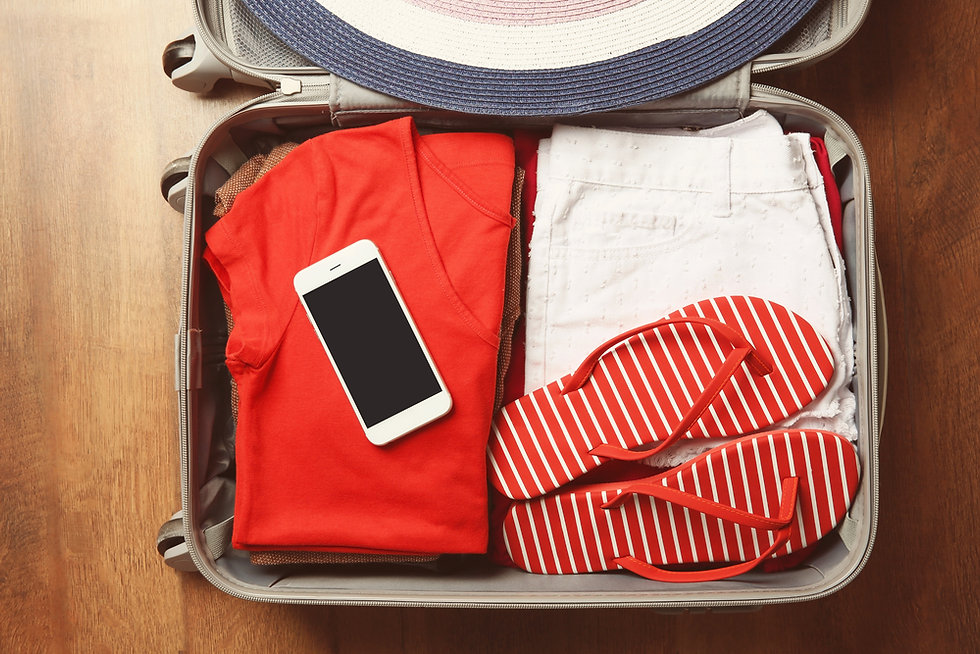 Phone on clothes in suitcase with flip-flops.jpg